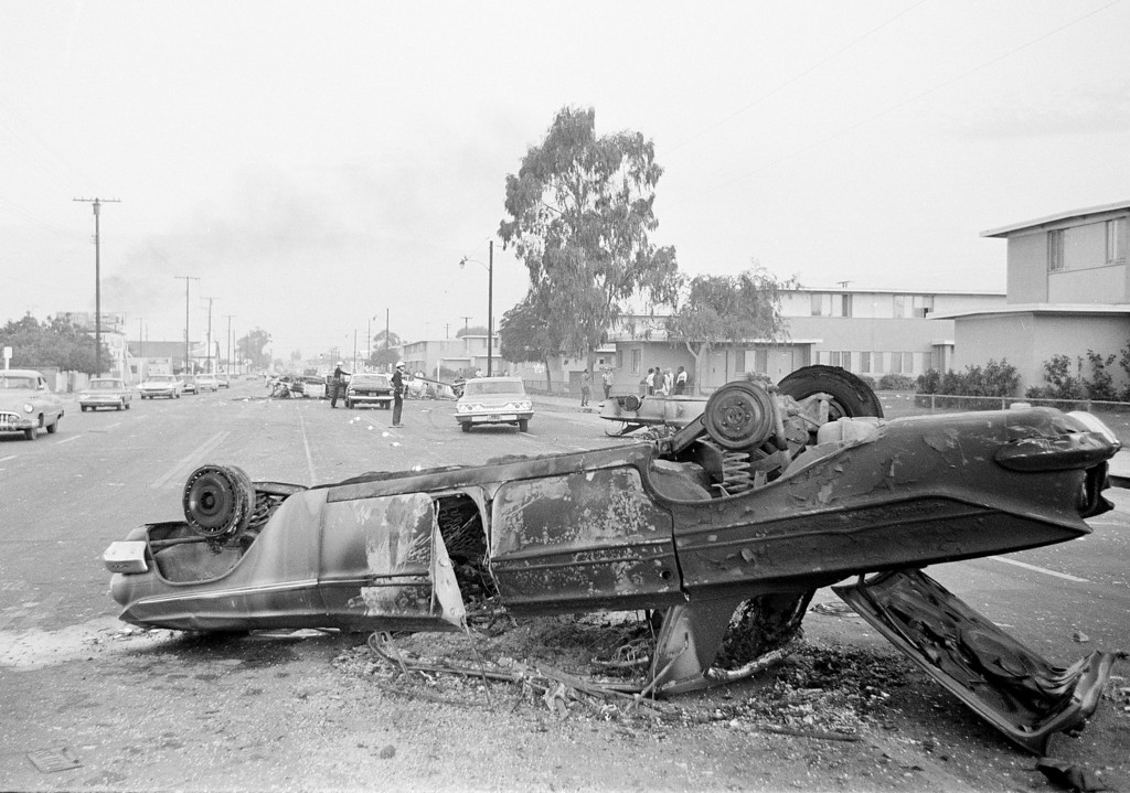 . An overturned automobile blocks the street in the Watts section of Los Angeles as day breaks at the scene of last night\'s rioting, Aug. 13, 1965. In the background are other burned cars. The scene is near the intersection of Imperial Highway and Avalon. (AP Photo/Harold Filan)