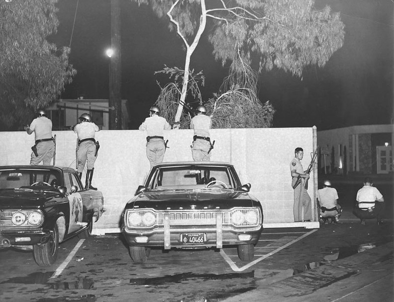 . Deputies are shown with 12-gauge shotguns holding the Firestone Sheriffs Station under arms in anticipation of attack by rioters in the Watts area.  (1965/Los Angeles Public Library)