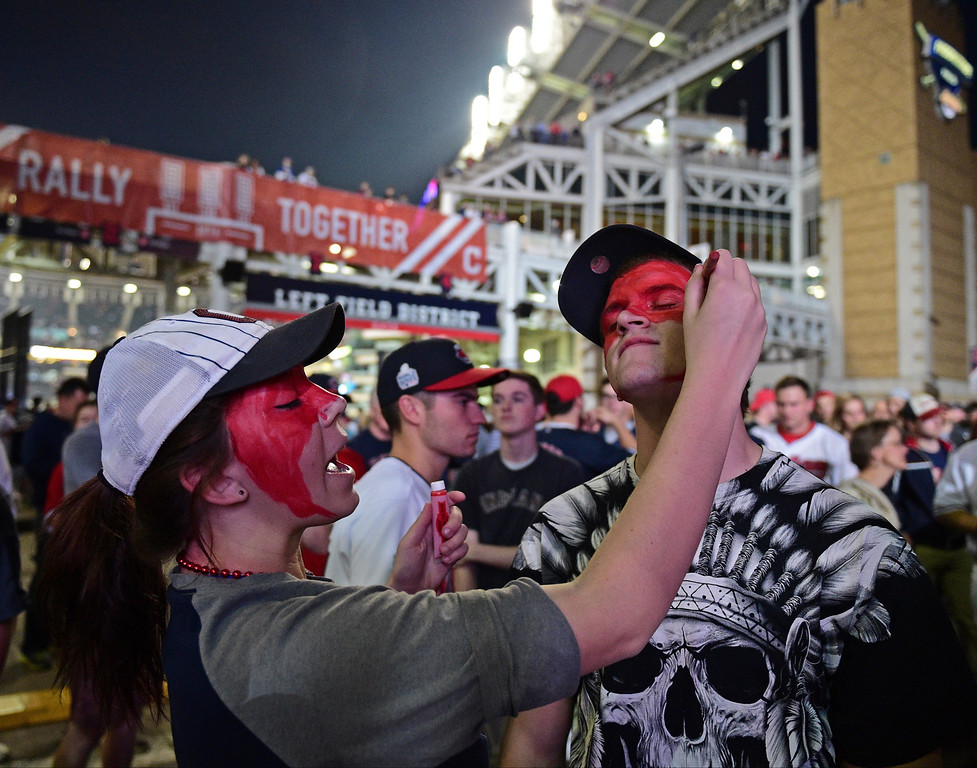 . Cleveland Indians fan Leah Krankowski, left, paints the face of Chris Diz during a watch party for Game 7 of the baseball World Series between the Indians and the Chicago Cubs, outside Progressive Field, Wednesday, Nov. 2, 2016, in Cleveland. (AP Photo/David Dermer)
