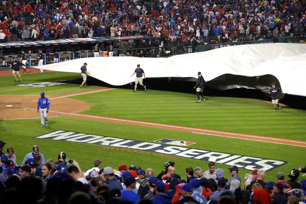 . CLEVELAND, OH - NOVEMBER 02:  Grounds crew put a tarp on the field as the game is delayed due to rain before the start of the 10th inning between the Chicago Cubs and the Cleveland Indians in Game Seven of the 2016 World Series at Progressive Field on November 2, 2016 in Cleveland, Ohio.  (Photo by Jamie Squire/Getty Images)