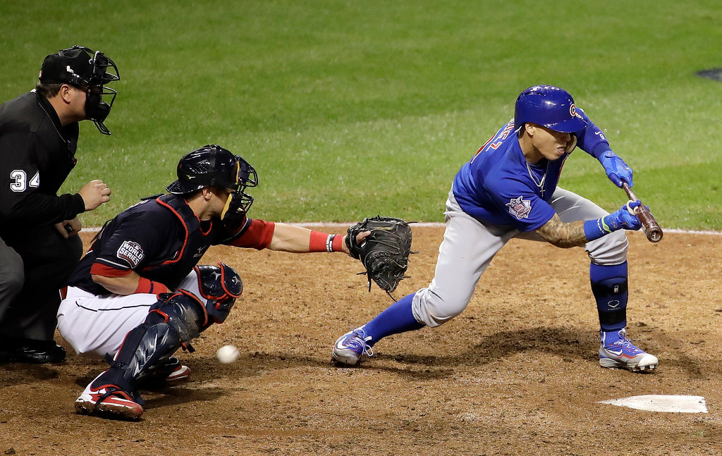 . Chicago Cubs\' Javier Baez strikes out on a bunt attempt during the ninth inning of Game 7 of the Major League Baseball World Series against the Cleveland Indians Wednesday, Nov. 2, 2016, in Cleveland. (AP Photo/Gene J. Puskar)