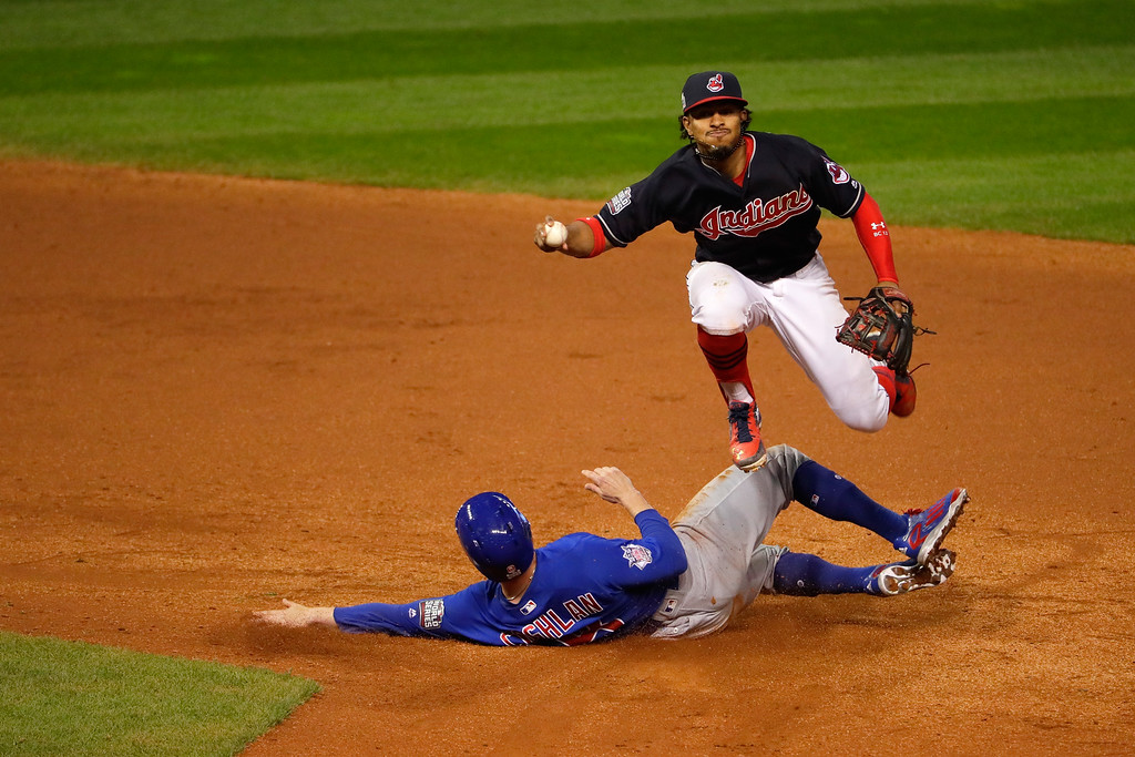 . CLEVELAND, OH - NOVEMBER 02:  Francisco Lindor #12 of the Cleveland Indians jumps over Chris Coghlan #8 of the Chicago Cubs as Coghlan is out at second base in the ninth inning in Game Seven of the 2016 World Series at Progressive Field on November 2, 2016 in Cleveland, Ohio.  (Photo by Jamie Squire/Getty Images)