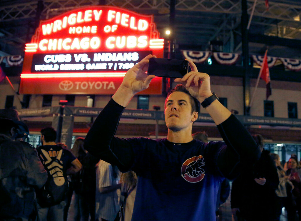 . Chicago Cubs fan Jake Casper from Mount Prospect, Ill., photographs outside Wrigley Field in Chicago, shortly before the beginning of Game 7 of the Major League Baseball World Series between the Cubs and the Cleveland Indians in Cleveland, Wednesday, Nov. 2, 2016. (AP Photo/Charles Rex Arbogast)