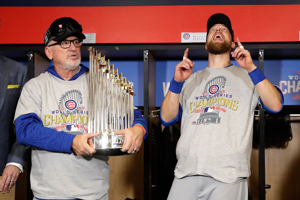 . CLEVELAND, OH - NOVEMBER 02:  Manager Joe Maddon of the Chicago Cubs poses with The Commissioner\'s Trophy as Ben Zobrist #18 reacts after the Chicago Cubs defeated the Cleveland Indians 8-7 in Game Seven of the 2016 World Series at Progressive Field on November 2, 2016 in Cleveland, Ohio. The Cubs win their first World Series in 108 years.  (Photo by David J. Phillip-Pool/Getty Images)