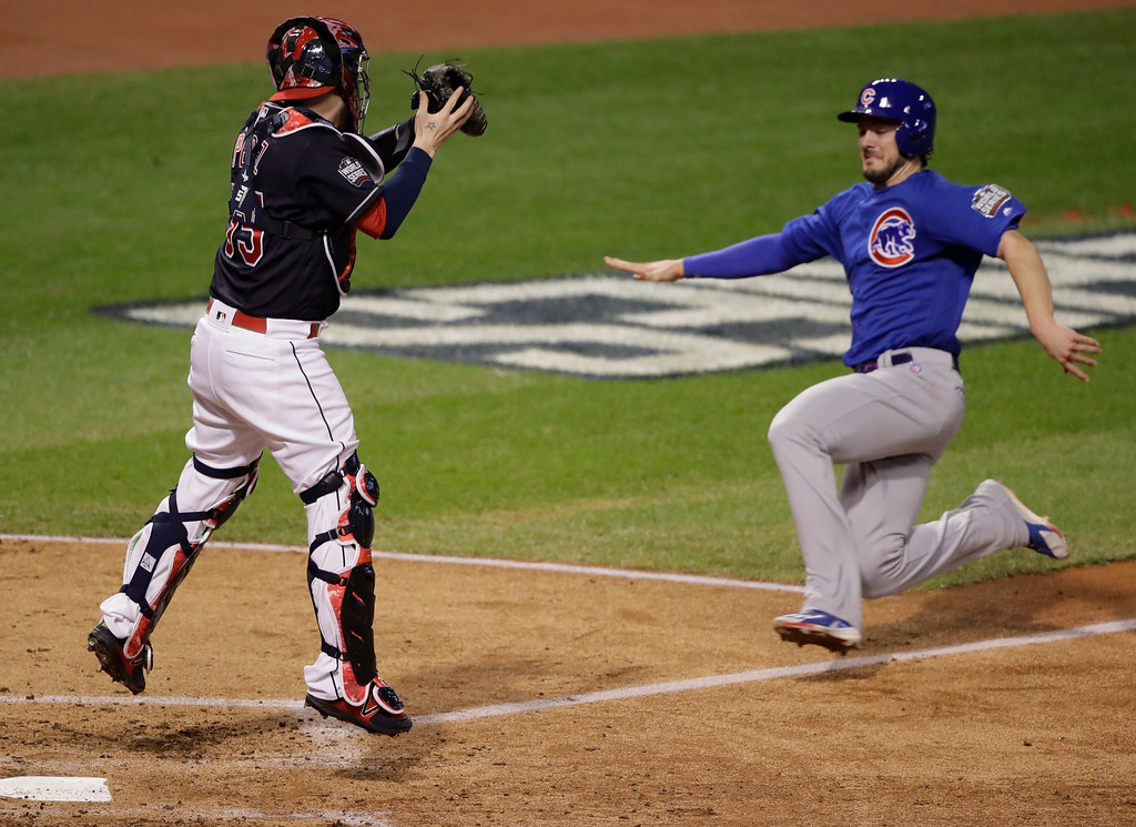. Chicago Cubs\' Kris Bryant slides home and scores as Cleveland Indians catcher Roberto Perez looks to make the tag during the fourth inning of Game 7 of the Major League Baseball World Series Wednesday, Nov. 2, 2016, in Cleveland. (AP Photo/Gene J. Puskar)