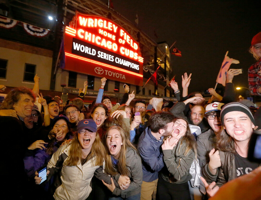 . Chicago Cubs fans celebrate in front of Wrigley Field in Chicago on Wednesday night, Nov. 2, 2016, after the Cubs defeated the Cleveland Indians 8-7 in Game 7 of the baseball World Series in Cleveland. (AP Photo/Charles Rex Arbogast)