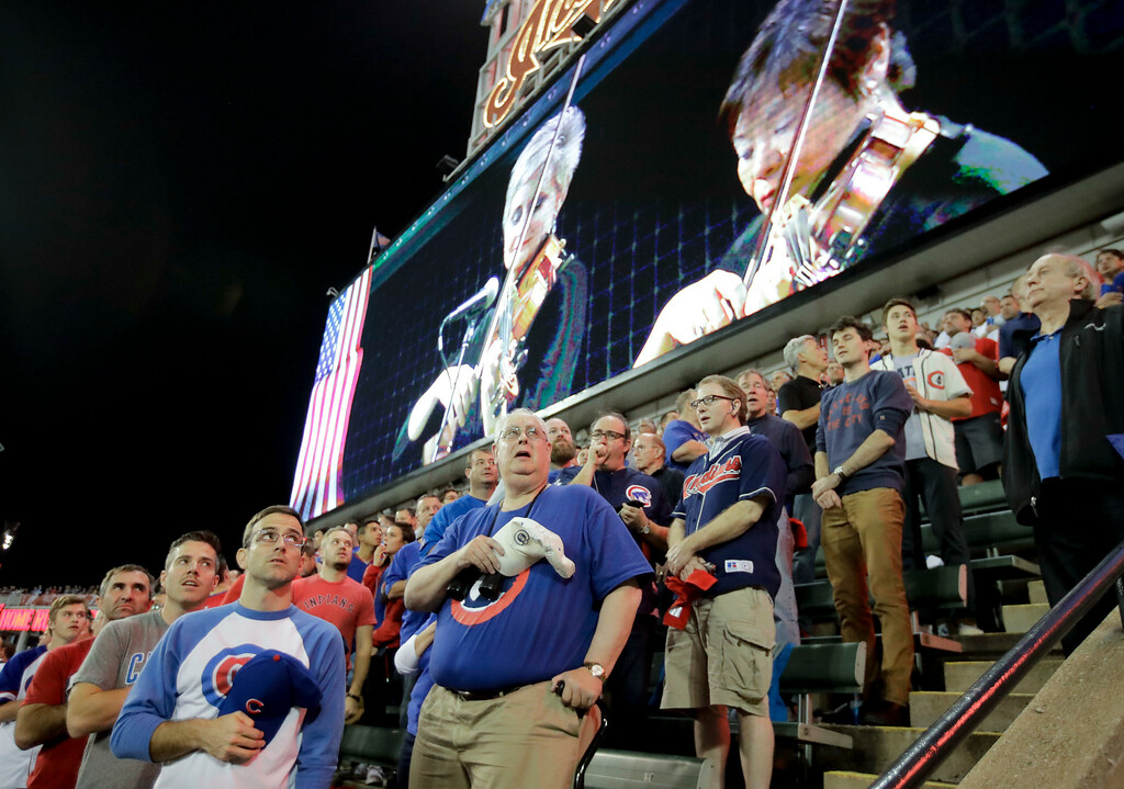 . Fans stand as the string section of the Cleveland Orchestra plays an instrumental performance of the national anthem before Game 7 of the Major League Baseball World Series between the Cleveland Indians and the Chicago Cubs Wednesday, Nov. 2, 2016, in Cleveland. (AP Photo/Charlie Riedel)