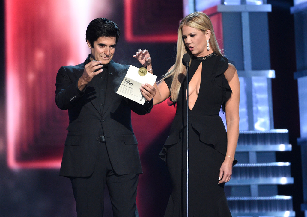 . The award envelope smokes as David Copperfield, left, and Nancy O\'Dell present the award for song of the year at the 52nd annual Academy of Country Music Awards at the T-Mobile Arena on Sunday, April 2, 2017, in Las Vegas. (Photo by Chris Pizzello/Invision/AP)