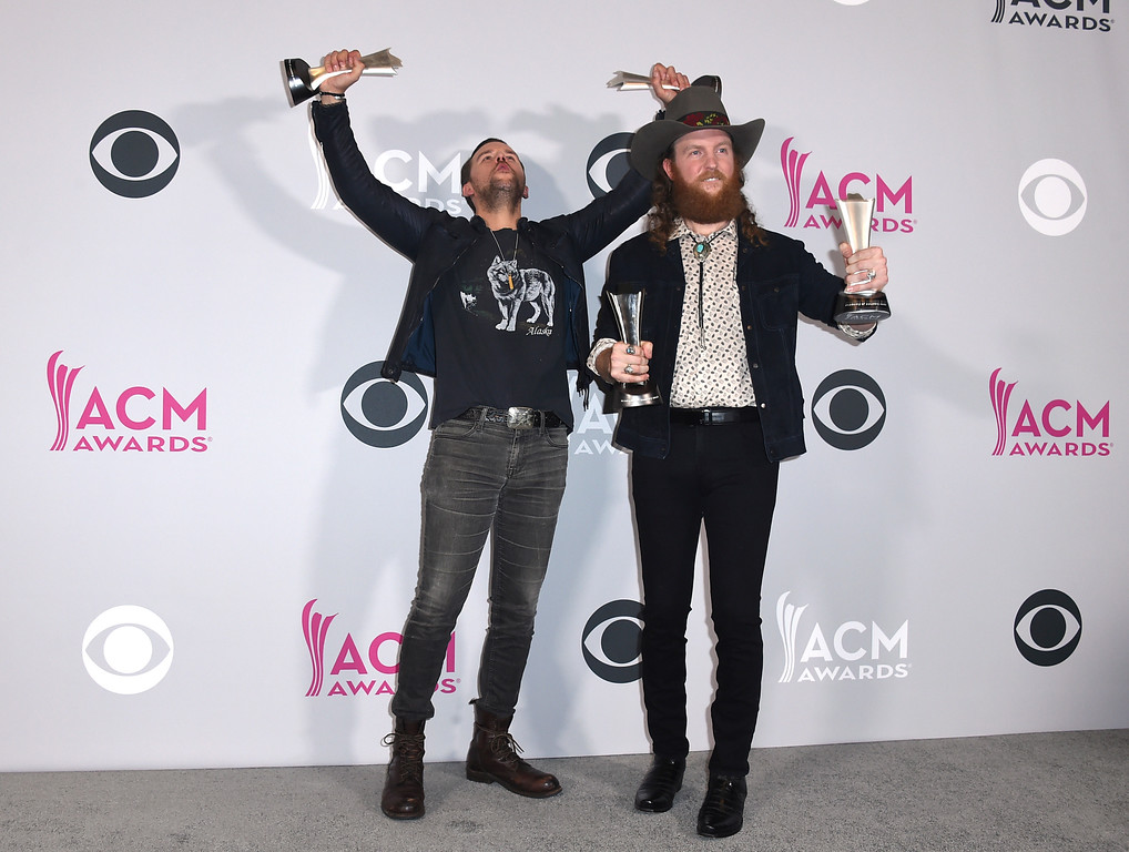 . T.J. Osborne, left, and John Osborne, of Brothers Osborne, pose in the press room with their awards for vocal duo of the year, and new vocal/duo group of the year at the 52nd annual Academy of Country Music Awards at the T-Mobile Arena on Sunday, April 2, 2017, in Las Vegas. (Photo by Jordan Strauss/Invision/AP)