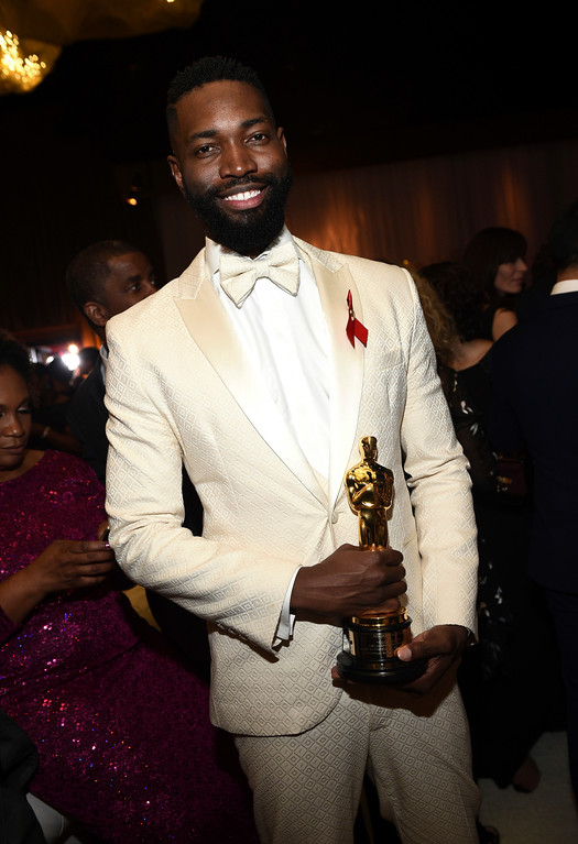 """. Tarell Alvin McCraney poses with his award for best adapted screenplay for \""""Moonlight\"""" at the Governors Ball after the Oscars on Sunday, Feb. 26, 2017, at the Dolby Theatre in Los Angeles. (Photo by Al Powers/Invision/AP)"""