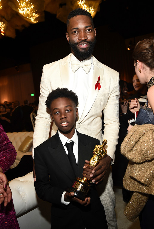 """. Tarell Alvin McCraney, behind, and Alex R. Hibbert pose with Tarell\'s award for best adapted screenplay for \""""Moonlight\"""" at the Governors Ball after the Oscars on Sunday, Feb. 26, 2017, at the Dolby Theatre in Los Angeles. (Photo by Al Powers/Invision/AP)"""