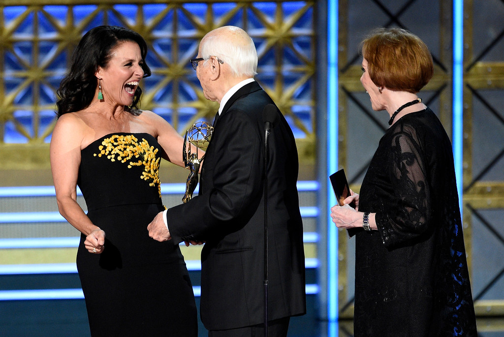 """. Norman Lear, center, and Carol Burnett, right, present the award for outstanding comedy series for \""""Veep\"""" to Julia Louis-Dreyfus at the 69th Primetime Emmy Awards on Sunday, Sept. 17, 2017, at the Microsoft Theater in Los Angeles. (Photo by Chris Pizzello/Invision/AP)"""