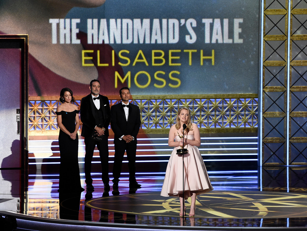 ". Elisabeth Moss, center, accepts the award for outstanding lead actress in a drama series for ""The Handmaid\'s Tale\"" while Tatiana Maslany, left, and Jeffrey Dean Morgan, right, look on at the 69th Primetime Emmy Awards on Sunday, Sept. 17, 2017, at the Microsoft Theater in Los Angeles. (Photo by Chris Pizzello/Invision/AP)"