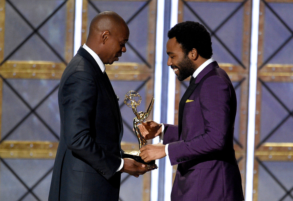 ". Dave Chappelle, left, presents the award for outstanding directing for a comedy series for the ""Atlanta\"" episode \""B.A.N.\"" to Donald Glover at the 69th Primetime Emmy Awards on Sunday, Sept. 17, 2017, at the Microsoft Theater in Los Angeles. (Photo by Chris Pizzello/Invision/AP)"