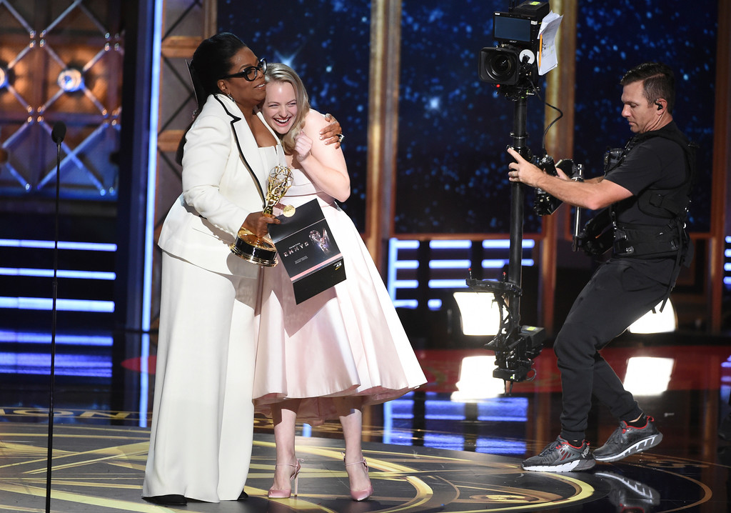 """. Oprah Winfrey, left, embraces Elisabeth Moss after \""""The Handmaid\'s Tale\"""" wins outstanding drama series at the 69th Primetime Emmy Awards on Sunday, Sept. 17, 2017, at the Microsoft Theater in Los Angeles. (Photo by Phil McCarten/Invision for the Television Academy/AP Images)"""