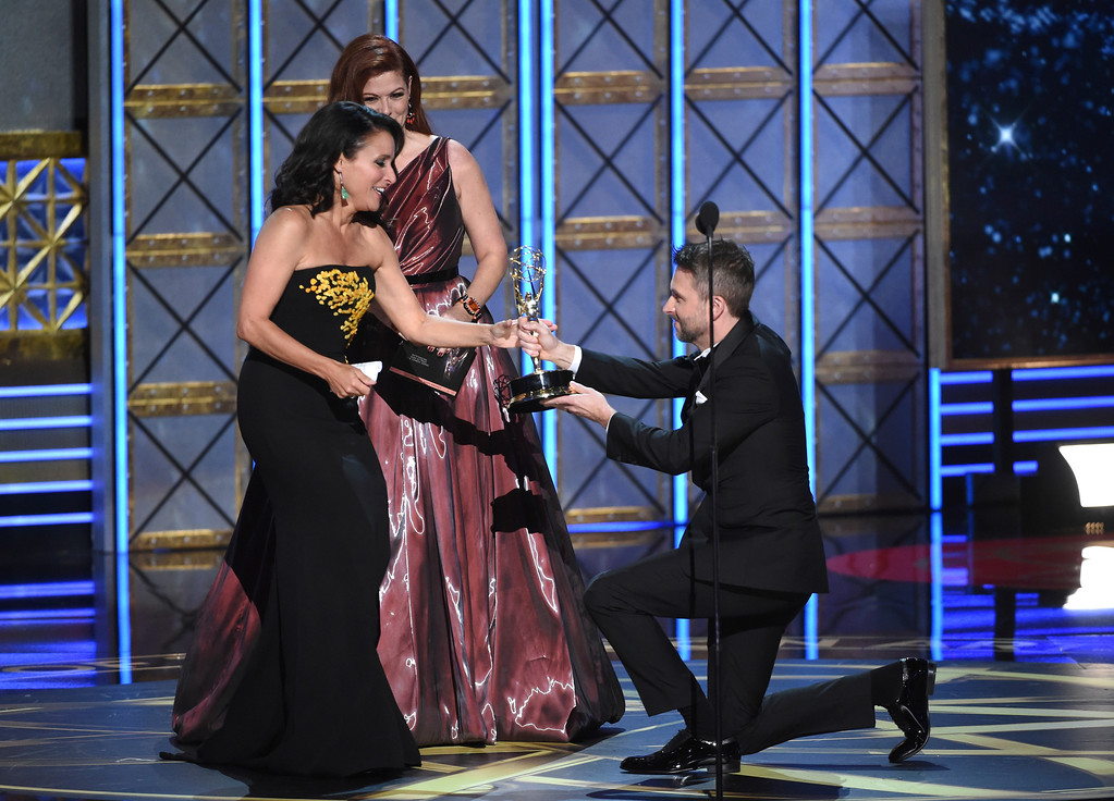 """. Julia Louis-Dreyfus, left, accepts the award for outstanding lead actress in a comedy series for \""""Veep\"""" from Debra Messing, center, and Chris Hardwick at the 69th Primetime Emmy Awards on Sunday, Sept. 17, 2017, at the Microsoft Theater in Los Angeles. (Photo by Phil McCarten/Invision for the Television Academy/AP Images)"""