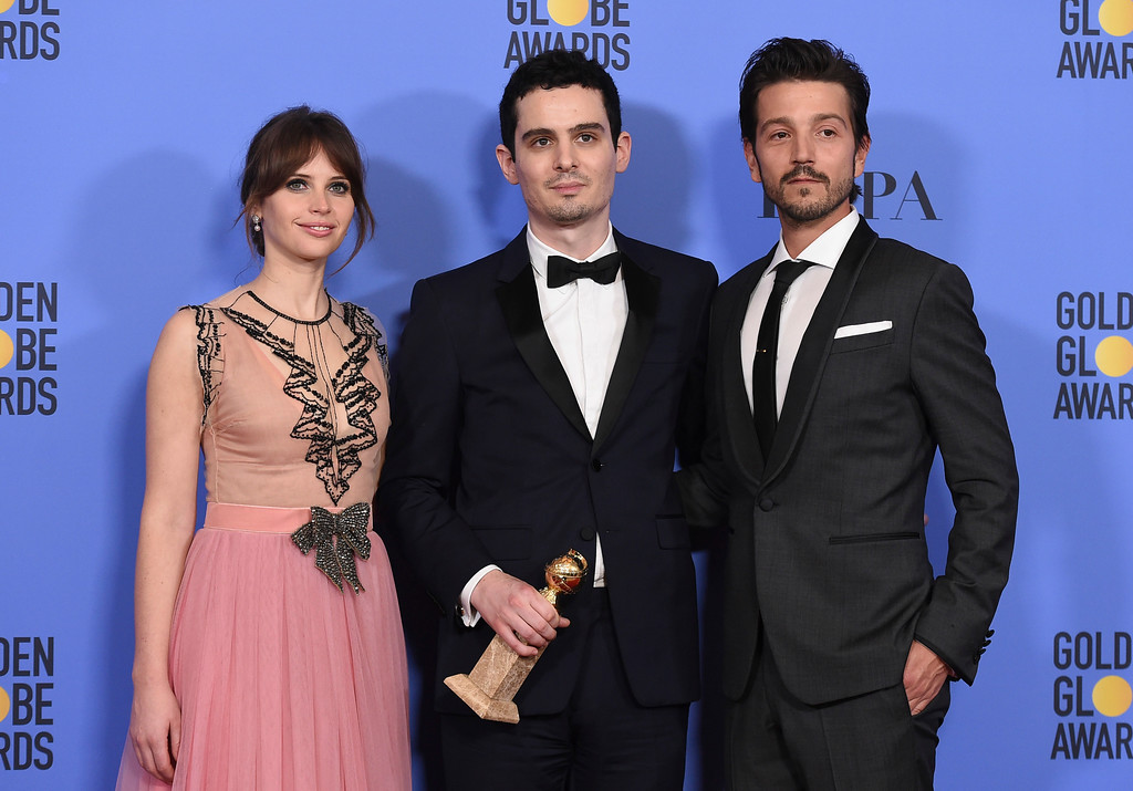 ". Damien Chazelle, center, winner of the award for best screenplay - motion picture for ""La La Land\"" poses with presenters Felicity Jones, left, and Diego Luna at the 74th annual Golden Globe Awards at the Beverly Hilton Hotel on Sunday, Jan. 8, 2017, in Beverly Hills, Calif. (Photo by Jordan Strauss/Invision/AP)"