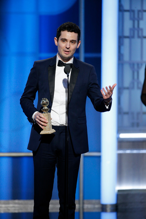 ". This image released by NBC shows Damien Chazelle with the award for best screenplay for ""La La Land,\"" at the 74th Annual Golden Globe Awards at the Beverly Hilton Hotel in Beverly Hills, Calif., on Sunday, Jan. 8, 2017. (Paul Drinkwater/NBC via AP)"