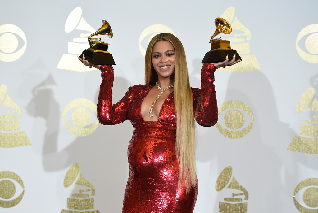 """. Beyonce poses in the press room with the awards for best music video for \""""Formation\"""" and best urban contemporary album for \""""Lemonade\"""" at the 59th annual Grammy Awards at the Staples Center on Sunday, Feb. 12, 2017, in Los Angeles. (Photo by Chris Pizzello/Invision/AP)"""