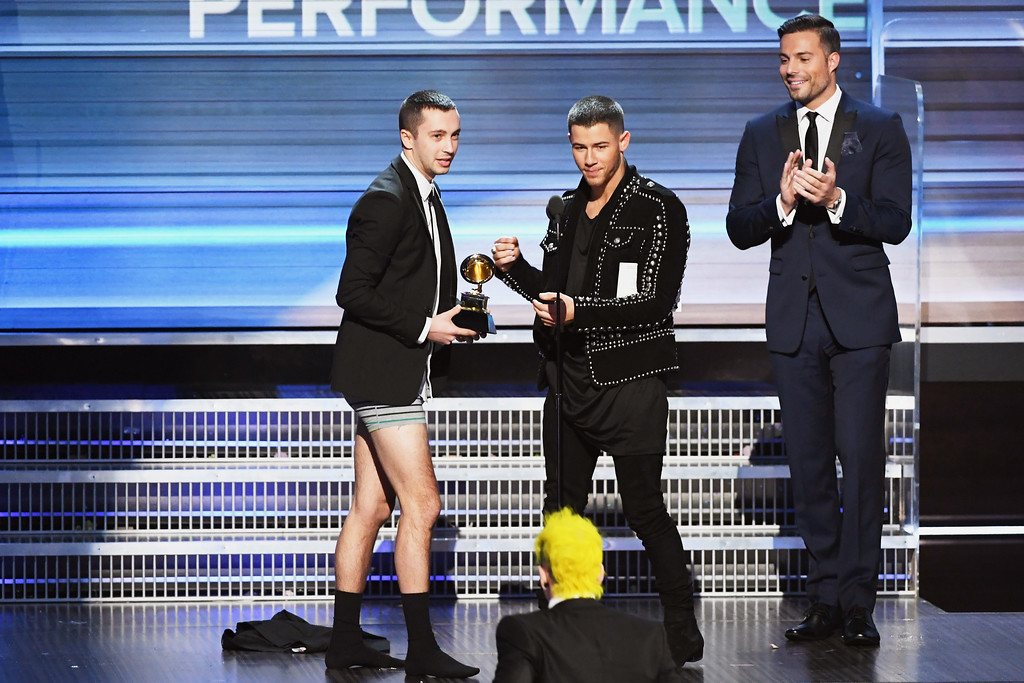 . LOS ANGELES, CA - FEBRUARY 12:  Recording artist Nick Jonas (C) presents the the Best Pop Duo/Group Performance award for \'Stressed Out\' to recording artist Tyler Joseph (L) of music group Twenty One Pilots onstage during The 59th GRAMMY Awards at STAPLES Center on February 12, 2017 in Los Angeles, California.  (Photo by Kevin Winter/Getty Images for NARAS)