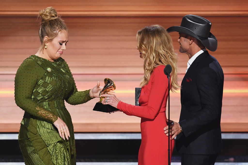 . LOS ANGELES, CA - FEBRUARY 12:  (L-R) Recording artist Adeles accepts the Album Of The Year award for \'25\' from recording artists Faith Hill and Tim McGraw onstage during The 59th GRAMMY Awards at STAPLES Center on February 12, 2017 in Los Angeles, California.  (Photo by Kevin Winter/Getty Images for NARAS)