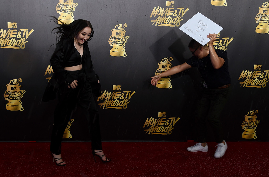 . Noah Cyrus reacts during a rain and hail storm while arriving at the MTV Movie and TV Awards at the Shrine Auditorium on Sunday, May 7, 2017, in Los Angeles. (Photo by Richard Shotwell/Invision/AP)
