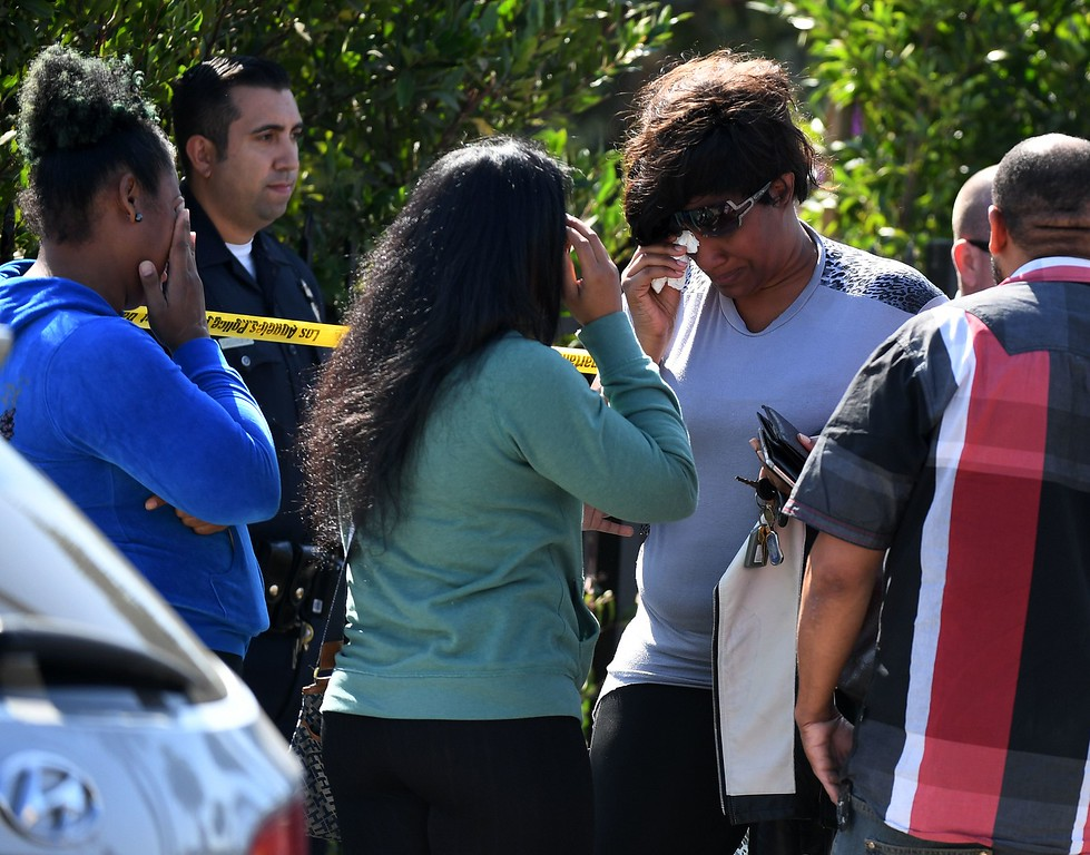 . Women cry at the scene where three people were killed during a shooting after a dispute at at a pop-up Jamaican restaurant in Los Angeles on October 15, 2016. Three people were killed and at least a dozen more injured, police said Saturday. One person has been arrested and police have launched a manhunt for another in connection with the deadly incident in West Adams, in the southwestern part of the metro area, said spokesman Lieutenant Chuck Springer.  (MARK RALSTON/AFP/Getty Images)