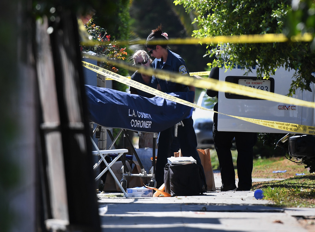 . A body is removed by the Los Angeles County coroner staff after three people were killed during a shooting after a dispute at a pop-up Jamaican restaurant in Los Angeles on October 15, 2016 Three people were killed and at least a dozen more injured, police said Saturday. One person has been arrested and police have launched a manhunt for another in connection with the deadly incident in West Adams, in the southwestern part of the metro area, said spokesman Lieutenant Chuck Springer.  (RALSTON/AFP/Getty Images)
