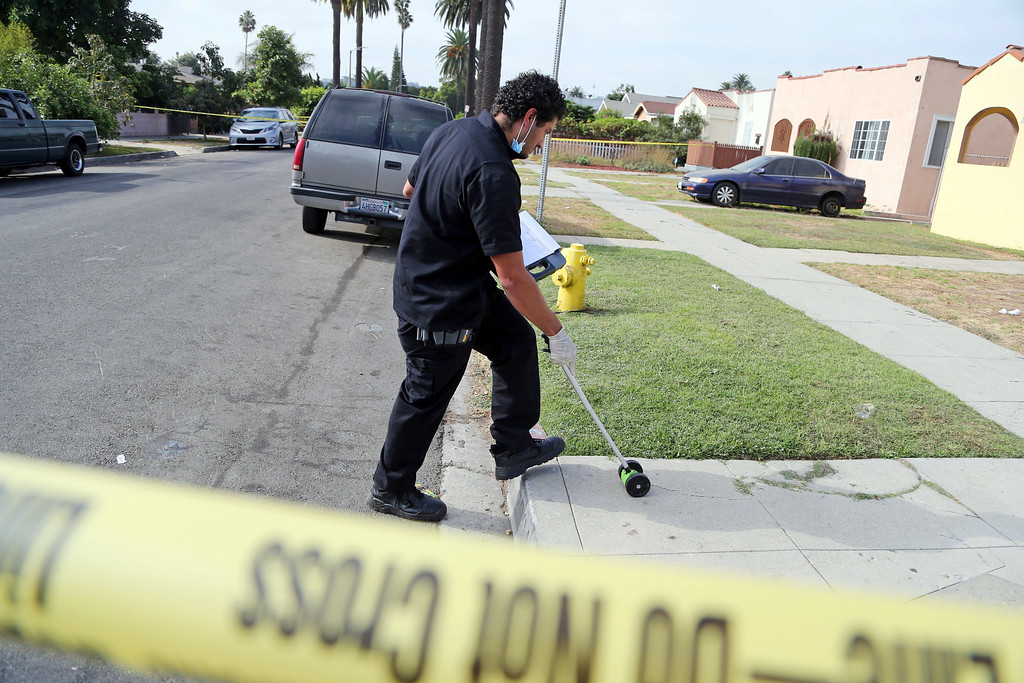 . A Los Angeles police investigator works the scene of a fatal shooting in the Crenshaw District neighborhood of Los Angeles, Saturday, Oct. 15, 2016.  According to police an early morning argument at a restaurant triggered gunfire.  (AP Photo/Reed Saxon)