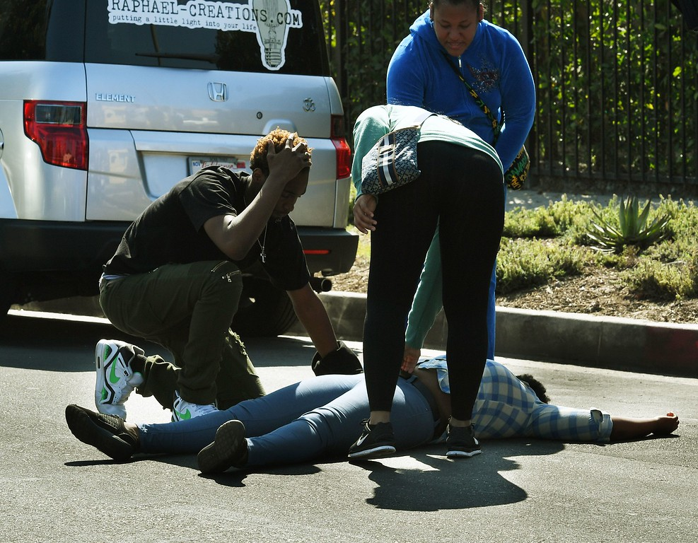 . A woman faints after discovering her partner and father of her child was among the three people killed during a shooting after a dispute at a pop-up Jamaican restaurant in Los Angeles on October 15, 2016 Three people were killed and at least a dozen more injured, police said Saturday. One person has been arrested and police have launched a manhunt for another in connection with the deadly incident in West Adams, in the southwestern part of the metro area, said spokesman Lieutenant Chuck Springer. (MARK RALSTON/AFP/Getty Images)