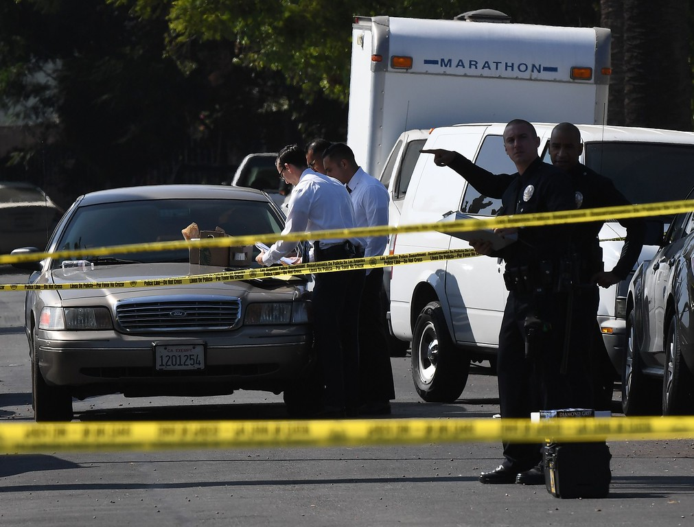. Police and investigators at the scene where three people killed during a shooting after a dispute at at a pop-up Jamaican restaurant in Los Angeles on October 15, 2016. Three people were killed and at least a dozen more injured, police said Saturday. One person has been arrested and police have launched a manhunt for another in connection with the deadly incident in West Adams, in the southwestern part of the metro area, said spokesman Lieutenant Chuck Springer. (MARK RALSTON/AFP/Getty Images)
