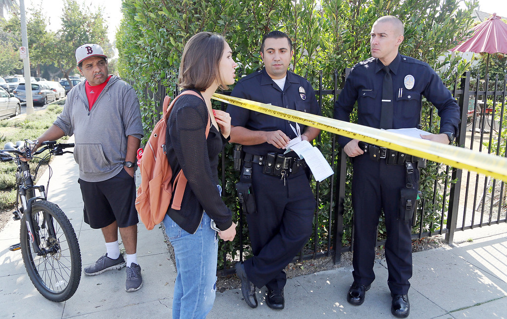 . An unidentified woman asks to cross a police line to see an area resident, but is denied entry, as Los Angeles police investigators Saturday, Oct. 15, 2016 work the scene of a shooting that left three people dead and 12 wounded at a restaurant operating in a home in a Crenshaw District neighborhood of Los Angeles just after midnight Saturday. Police who arrived at the scene in the working class neighborhood dotted by tall palm trees found shell casings and blood throughout the restaurant, located west of downtown Los Angeles. (AP Photo/Reed Saxon)