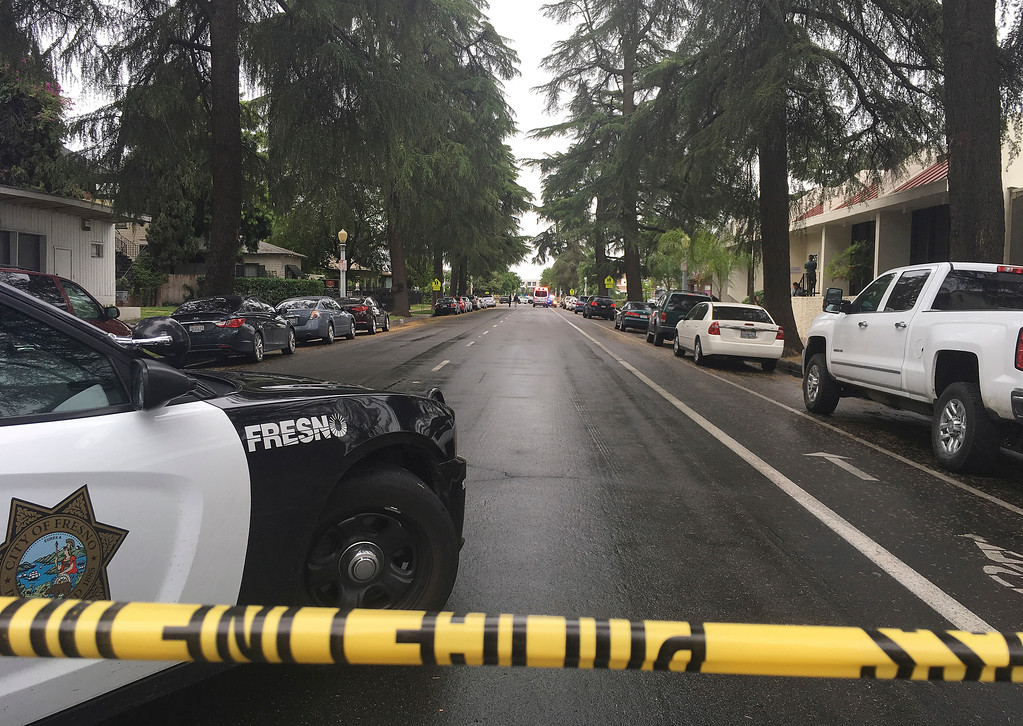 . A street is blocked off where emergency officials say a shooting has killed three people on Tuesday, April 18, 2017, in downtown Fresno, Calif.  A Fresno city spokesman says county offices are on lockdown, and people have been urged to shelter in place. (AP Photo/Scott Smith)