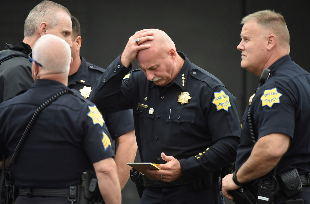 ". Fresno Police chief Jerry Dyer reviews notes on the triple fatal shooting before addressing the media Tuesday, April 18, 2017, in Fresno, Calif. A man shot and killed three people on the streets of downtown Fresno on Tuesday, shouting ""God is great\"" in Arabic during at least one of the slayings and later telling police that he hates white people, authorities said. Kori Ali Muhammad, 39, was arrested shortly after the rampage, whose victims were all white, police said. He also was wanted in connection with another killing days earlier, in which a security guard was gunned down at a Fresno motel after responding to a disturbance. (John Walker/Fresno Bee via AP)"