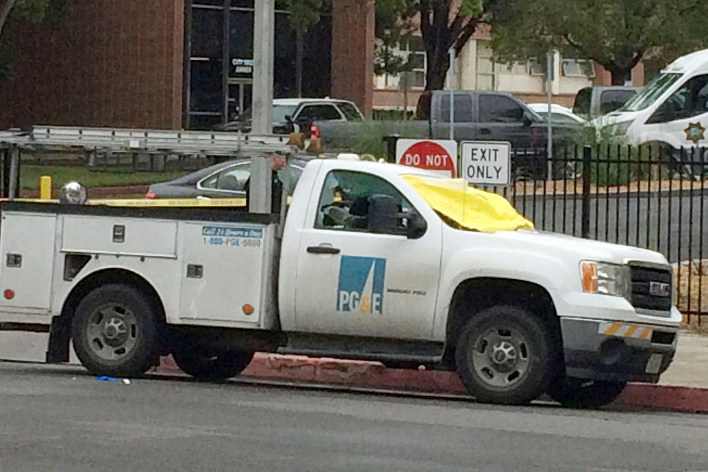 . A Pacific Gas and Electric vehicle that was shot at, with a yellow tarp covering the windshield, is parked in front of police headquarters Tuesday, April 18, 2017, in Fresno, Calif. Authorities say the man accused of shooting and killing three people in central California fired 16 rounds in one minute. Fresno Police Chief Jerry Dyer says 39-year-old Kori Ali Muhammad was armed with a revolver and reloaded at one point. He opened fire at four locations within a block. (Pablo Lopez/The Fresno Bee via AP)
