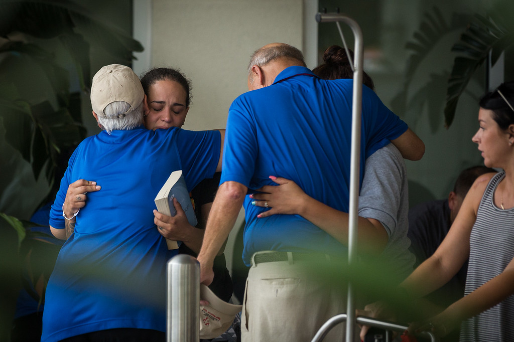 . People grieve outside a Hampton Inn & Suites hotel, which turned into a hub for families and friends waiting to hear about loved ones because of its proximity to the Orlando Regional Medical Center, in the wake of a mass shooting in Orlando, Fla., on Sunday, June 12, 2016. (Loren Elliott/Tampa Bay Times via AP)