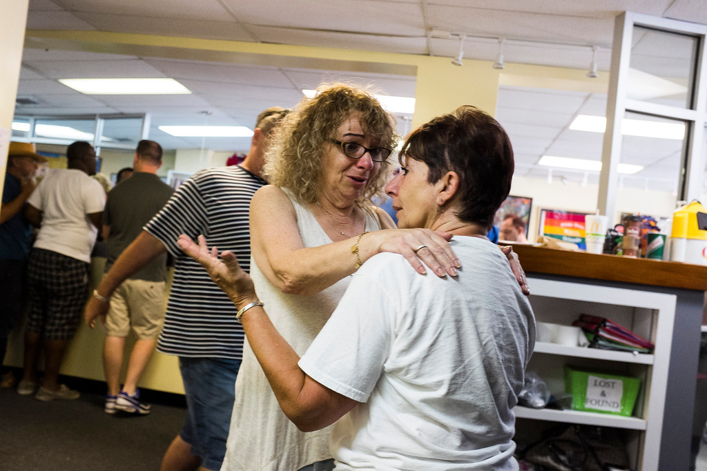 """. Volunteers Lesie Jampolsky and Dee \""""Mamma Dee\"""" Richer, console each other at the LGBTQ Community Center after the late night shooting at Pulse, an Orlando night club,on Sunday, June 12, 2016 in Orlando. A gunman wielding an assault-type rifle and a handgun opened fire inside a crowded Florida nightclub before dying in a gunfight with SWAT officers, police say. The attack left at least 50 people dead, making it the worst mass shooting in American history. (Zack Wittman/Tampa Bay Times via AP)"""