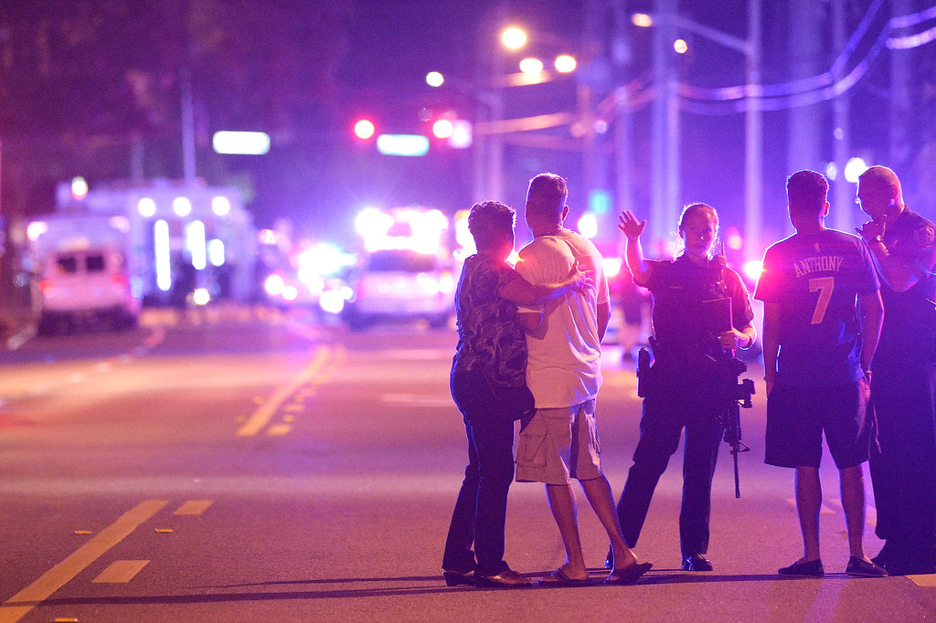 . Orlando Police officers direct family members away from a fatal shooting at Pulse Orlando nightclub in Orlando, Fla., Sunday, June 12, 2016. (AP Photo/Phelan M. Ebenhack)