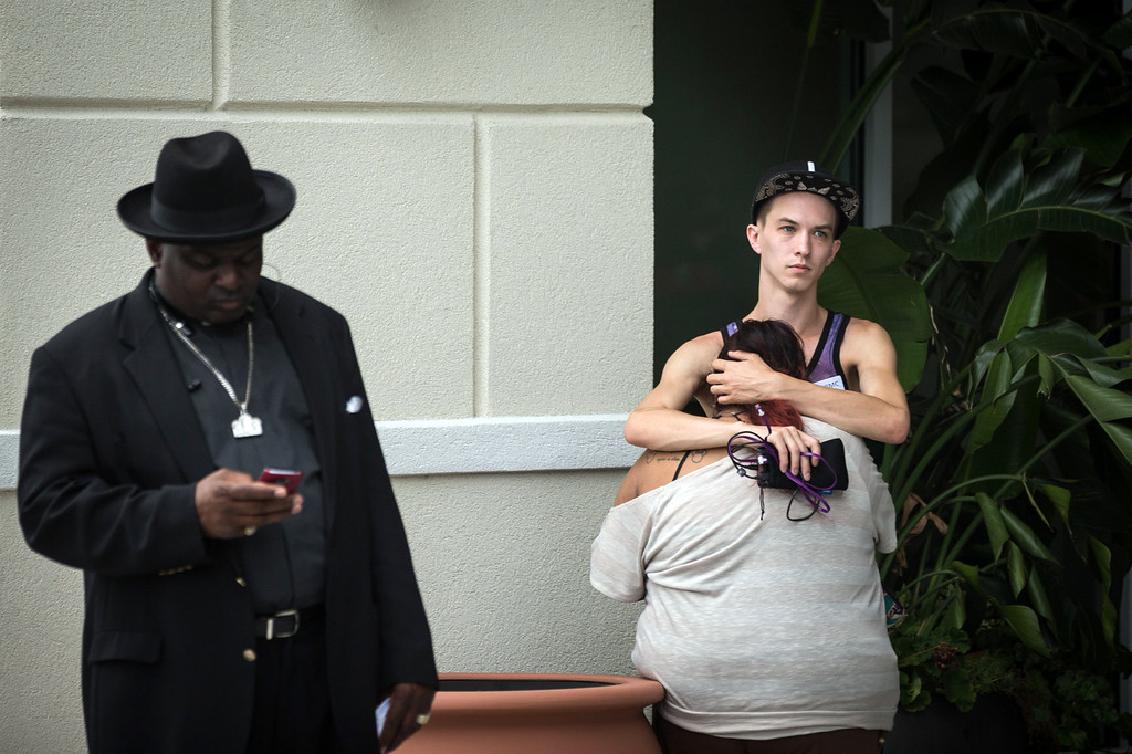 . People grieve outside a Hampton Inn & Suites hotel, which turned into a hub for families and friends waiting to hear about loved ones because of its proximity to the Orlando Regional Medical Center, in the wake of a mass shooting that took place the prior night in Orlando, Fla., on Sunday, June 12, 2016.  (Loren Elliott/The Tampa Bay Times via AP)