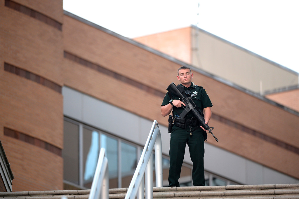 . A police officer stands guard outside the Orlando Regional Medical Center hospital after a fatal shooting at a nearby Pulse Orlando nightclub in Orlando, Fla., Sunday, June 12, 2016. (AP Photo/Phelan M. Ebenhack)