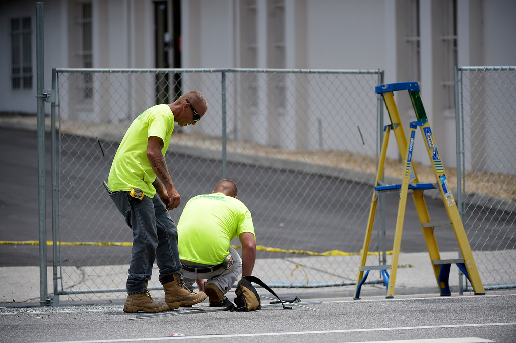 . Workers install a fence around the lot behind the Pulse nightclub after a shooting involving multiple fatalities at the nightclub in Orlando, Fla., Sunday, June 12, 2016. (AP Photo/Phelan M. Ebenhack)