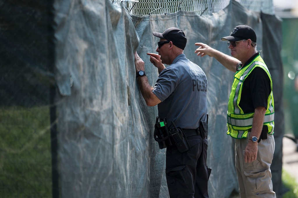. An Orlando police officer looks through a fence at FBI investigators behind the Pulse nightclub June 13, 2016 in Orlando, Florida. Forty-nine people died and more than 50 were injured early June 12 when a heavily-armed gunman opened fire and seized hostages at a gay nightclub in Orlando, Florida, in the worst mass shooting in US history. (BRENDAN SMIALOWSKI/AFP/Getty Images)