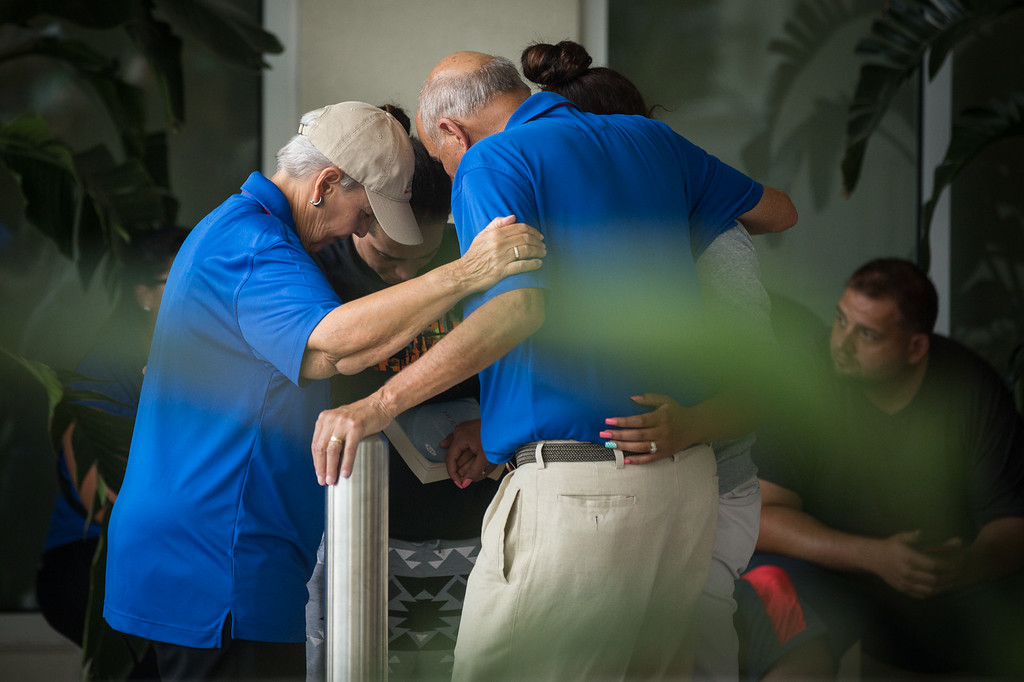 . People grieve outside a Hampton Inn & Suites hotel, which turned into a hub for families and friends waiting to hear about loved ones because of its proximity to the Orlando Regional Medical Center, in the wake of a mass shooting that took place the prior night in Orlando, Fla., on Sunday, June 12, 2016. (Loren Elliott/Tampa Bay Times via AP)