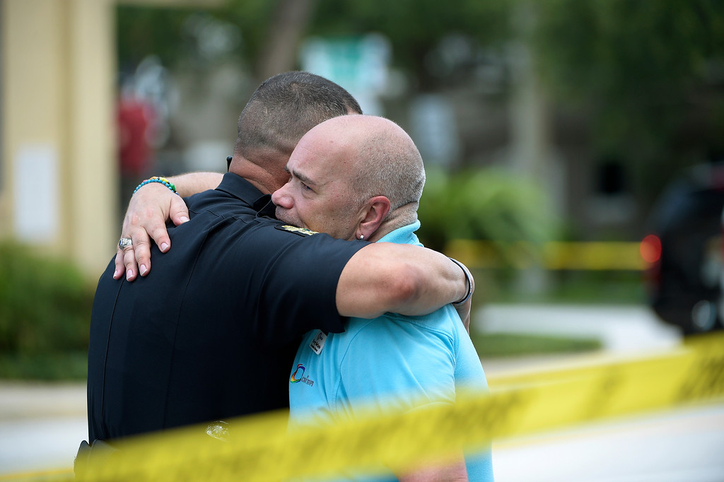 . Terry DeCarlo, executive director of the LGBT Center of Central Florida, right, is comforted by an Orlando Police officer after a shooting involving multiple fatalities at a nightclub in Orlando, Fla., Sunday, June 12, 2016. (AP Photo/Phelan M. Ebenhack)