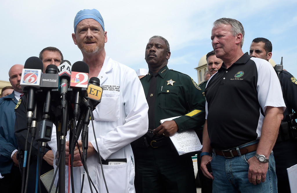 . Dr. Michael Cheatham, chief surgeon of the Orlando Health Regional Medical Center hospital, addresses reporters during a news conference after a shooting involving multiple fatalities at a nightclub in Orlando, Fla., Sunday, June 12, 2016. Watching are Orange County Sheriff Jerry Demings, second from right, and Orlando Mayor Buddy Dyer. (AP Photo/Phelan M. Ebenhack)