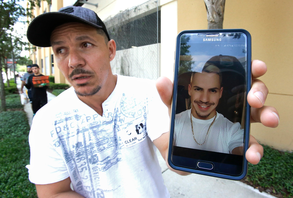. Angel Mendez, standing outside the Orlando Regional Medical Center, holds up a cell phone photo trying to get information about his brother Jean C. Mendez that was at the Pulse Nightclub where a shooting involving multiple fatalities occurred, Sunday, June 12, 2016, in Orlando, Fla. (AP Photo/John Raoux)