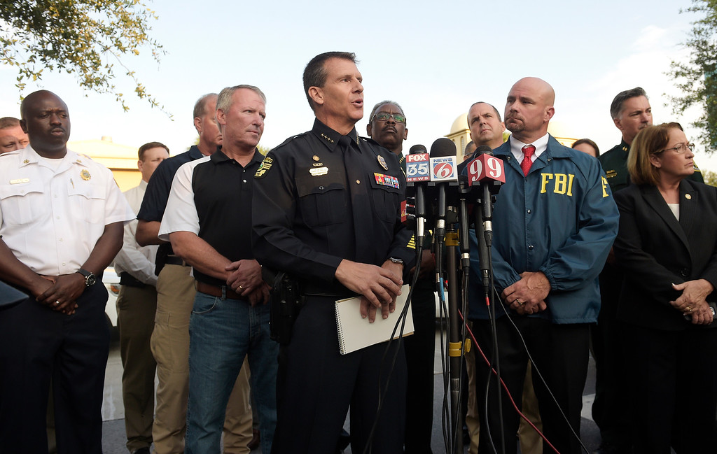 . Orlando Police Chief John Mina, center, addresses reporters during a news conference after a shooting involving multiple fatalities at a nightclub in Orlando, Fla., Sunday, June 12, 2016. (AP Photo/Phelan M. Ebenhack)