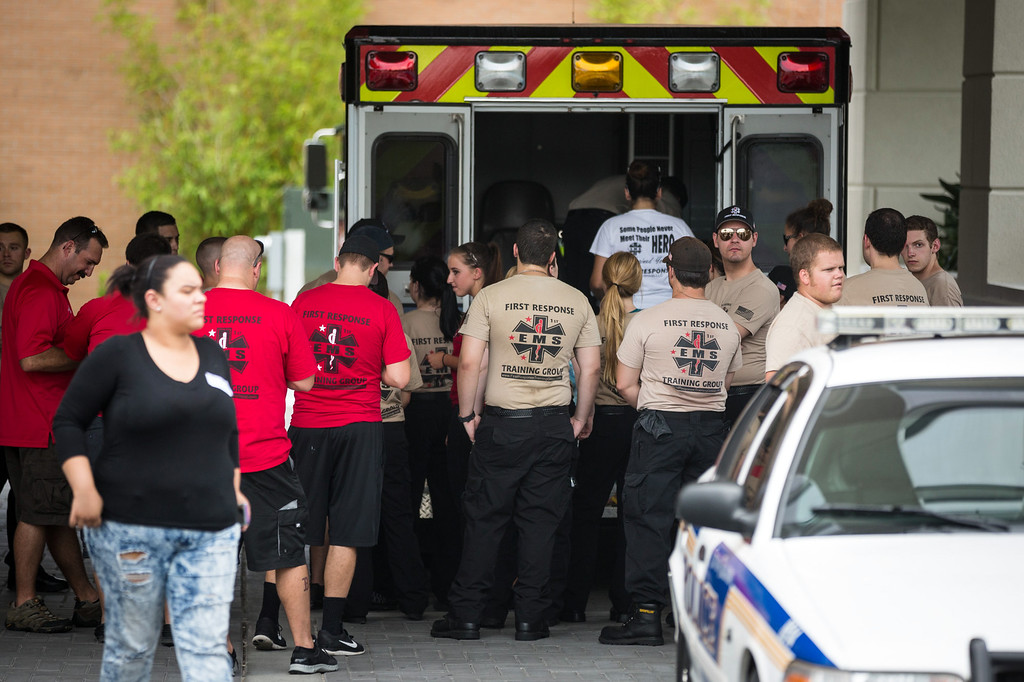 . EMS first response personnel are seen outside a Hampton Inn & Suites hotel, which turned into a hub for families and friends waiting to hear about loved ones because of its proximity to the Orlando Regional Medical Center, in the wake of a mass shooting that took place the prior night in Orlando, Fla., on Sunday, June 12, 2016. (Loren Elliott/The Tampa Bay Times via AP)