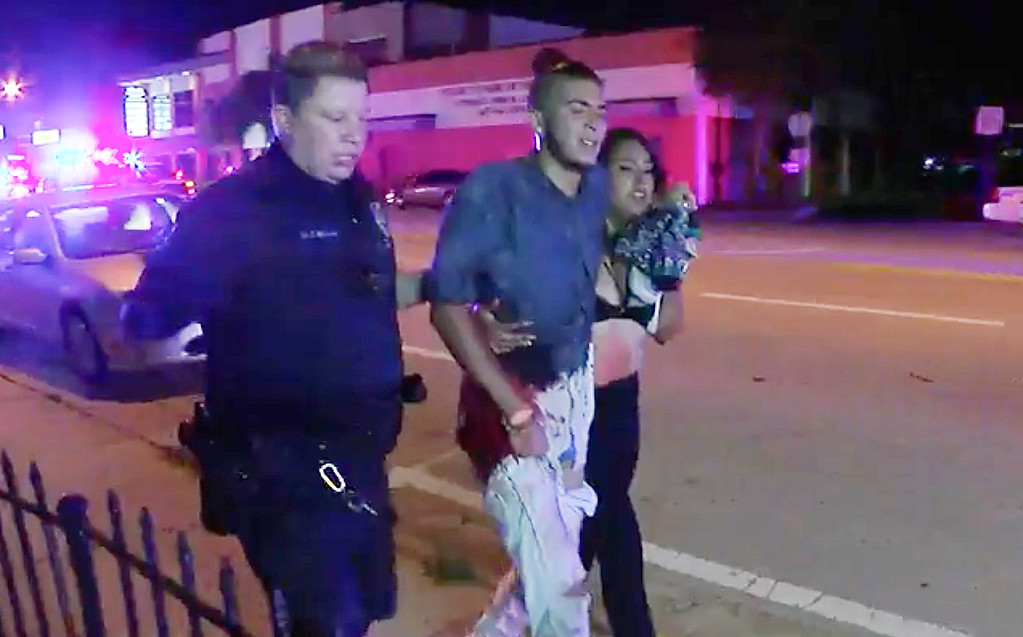 . An injured man is escorted out of the Pulse nightclub after a shooting rampage, Sunday morning June 12, 2016, in Orlando, Fla. A gunman wielding an assault-type rifle and a handgun opened fire inside a crowded gay nightclub killing 49 people before dying in a gunfight with SWAT officers. It was the deadliest mass shooting in American history.   (AP Photo/Steven Fernandez)