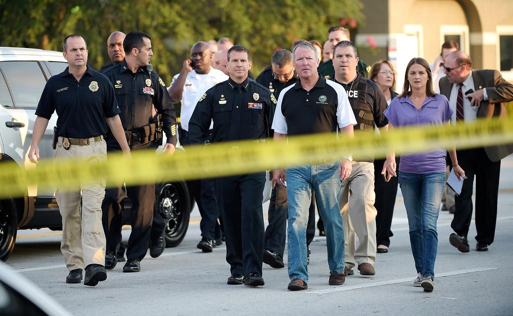 . Orlando Mayor Buddy Dyer, center right, and Orlando Police Chief John Mina, center left, arrive to a news conference after a fatal shooting at Pulse Orlando nightclub in Orlando, Fla., Sunday, June 12, 2016. (AP Photo/Phelan M. Ebenhack)